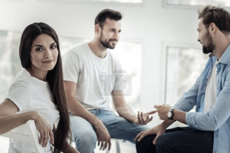 Photo for Female patient. Nice attractive young woman sitting with other patients and turning to you while having psychological therapy session - Royalty Free Image