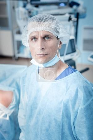 Photo for Surgical medicine. Smart confident male surgeon wearing scrubs and looking at you while being at work - Royalty Free Image