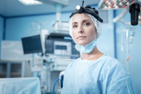 Photo for Female surgeon. Nice smart young woman wearing scrubs and standing in the operation theater while preparing for an operation - Royalty Free Image