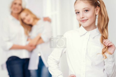 Photo for Children are our future. Selective focus on a cheerful little lady touching her ponytail and lightly smiling into the camera while her tender mother and grandmother hugging with love behind. - Royalty Free Image