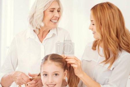 Foto de Diversión y alegría. Enfoque selectivo en una emocionada hermosa anciana sonriendo ampliamente mientras que habla a su hija madura y hacer colas de caballo para su nieta alegre - Imagen libre de derechos