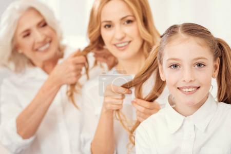 Adorable girl enjoying family hairstyles time at home