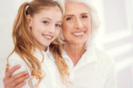 Portrait of beautiful senior lady embracing charming granddaughter