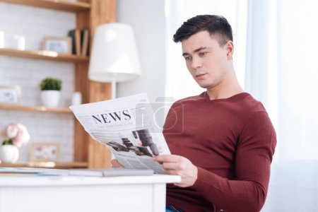 Smart male freelancer reading newspaper