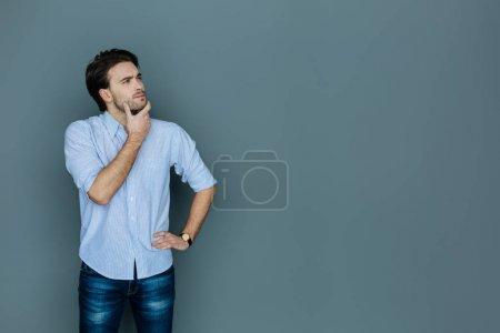 Photo pour Processus de réflexion. Beau beau jeune homme debout sur un grand fond et tenant son menton tout en pensant - image libre de droit