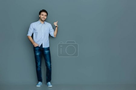 Cheerful positive man pointing with his finger