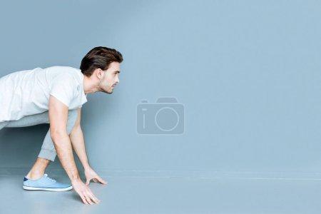 Photo pour Un sportif professionnel. Sérieux bel homme athlétique impatient et prêt à courir tout en participant à la compétition sportive - image libre de droit