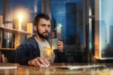 Photo pour Activités du soir. Calme jeune homme attentif regardant l'écran d'un ordinateur moderne assis à la table avec une tasse dans la main - image libre de droit