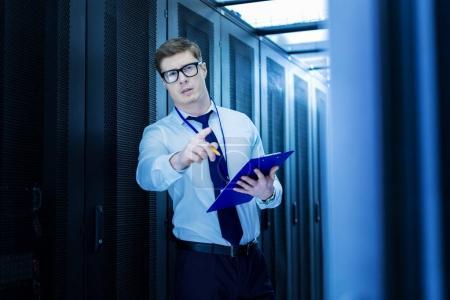 Foto de Oye, tú. Operador inteligente guapo sosteniendo una carpeta y señalando con su dedo - Imagen libre de derechos