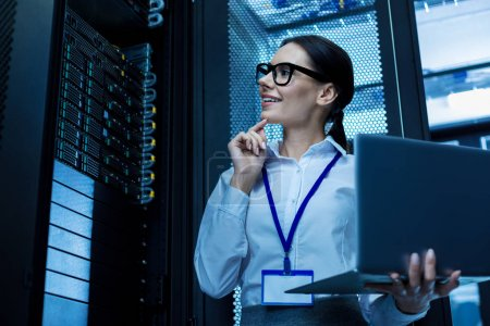 Cheerful operator working in a server cabinet