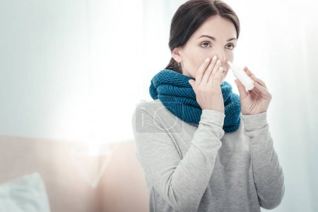 Serious ill woman using nose spray touching to her nose.