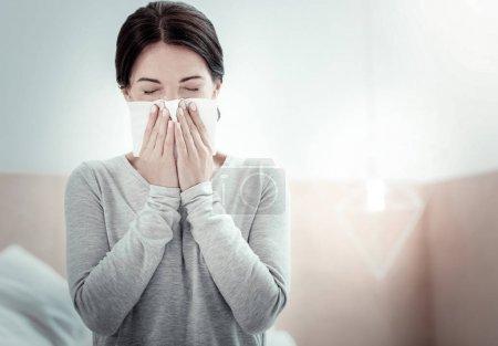 Photo pour Reste à la maison. Fatigué malade insatisfait femme assise dans la chambre les yeux fermés et éternuer . - image libre de droit