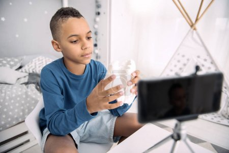 Reflective boy blogger explaining principles