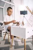 Energetic boy blogger using dinosaurs toys