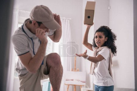 Photo for Dissatisfied customer. Angry young woman shouting at the courier while holding a box - Royalty Free Image