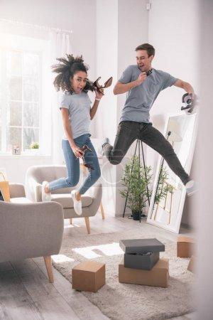 Photo pour Je m'amuse. Heureux couple enchanté sautant tout en s'amusant ensemble - image libre de droit