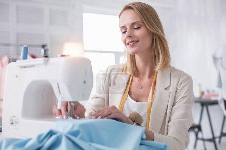 Glad female tailor sewing together