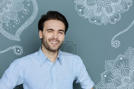 Close up of handsome cheerful man winking at you