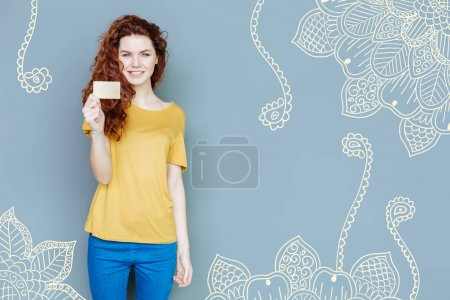 Delighted young girl showing credit card on pattern background