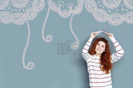Photo pour Je m'amuse. Portrait de fille agréable positive avec les cheveux bouclés regardant vers le haut tout en gardant livre ouvert au-dessus de sa tête sur fond de motif rose - image libre de droit