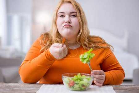 Determined fat woman eating healthy breakfast
