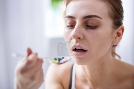 Photo for Serious sickness. Cheerless young woman taking medicine while being seriously ill - Royalty Free Image