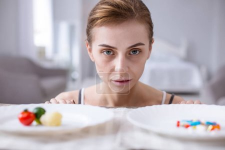 Sad pale woman standing in front of plates