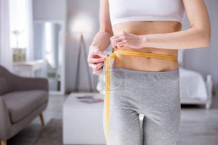 Nice slim woman measuring her waist