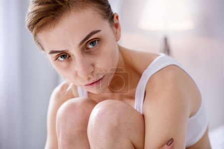 Sad underweight woman sitting on the bed