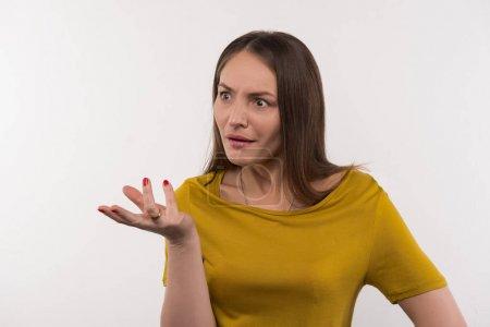 Photo pour Langage du corps. Belle femme émotionnelle permanent sur fond blanc et gesticulant avec ses mains - image libre de droit
