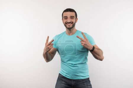 Photo for Great mood. Joyful positive man showing V signs while looking at you - Royalty Free Image