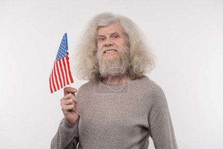 Cheerful nice man holding the US flag