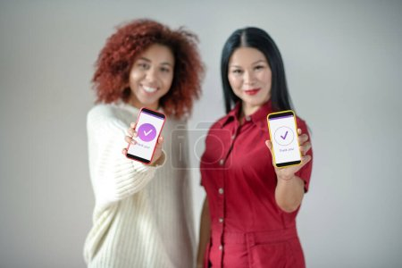 Photo for Using social media. Cheerful best friends holding smartphones while using social media - Royalty Free Image