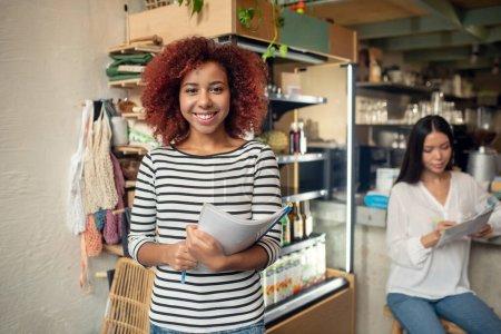 Photo pour Propriétaire d'un café. Belle jeune femme frisée possédant un café avec un ami se sentant heureux - image libre de droit