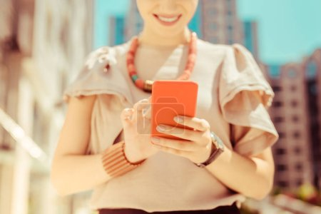 Photo for Let me check. Close up of happy female that keeping smile on her face while looking at screen of her gadget - Royalty Free Image