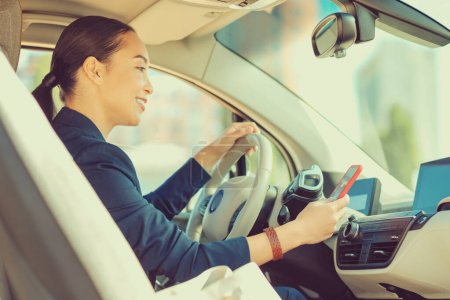 Photo for Good news. Pleased brunette woman keeping smile on her face while sitting in her car - Royalty Free Image