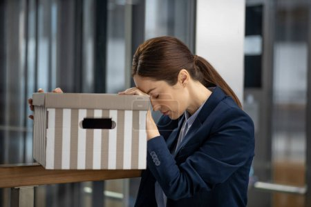 Photo pour Après avoir perdu son emploi. Femme aux cheveux bruns portant une veste sombre se sentant mal après avoir perdu son emploi de façon inattendue - image libre de droit