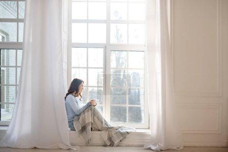 Photo pour Harmonie matinale. Jeune femme aux cheveux foncés regardant par la fenêtre - image libre de droit