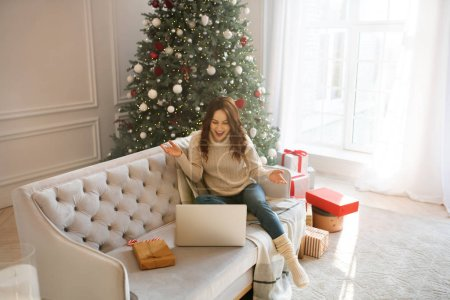 Photo for Online. Dark-haired woman near christmas tree having a video talk - Royalty Free Image