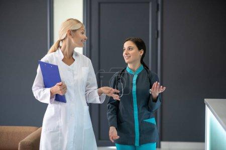 Photo pour Parler à un stagiaire. Un médecin principal en robe blanche discute avec un jeune stagiaire - image libre de droit