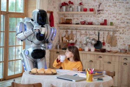 Photo pour Pause pour le thé. Cute girl and robot having tea together while having a break in doing homework - image libre de droit