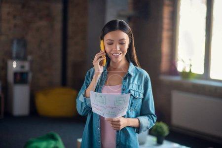 Photo pour Parler au téléphone. Femme intelligente et positive regardant ses notes au téléphone - image libre de droit