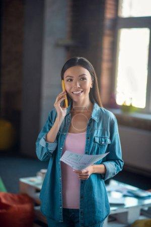 Photo pour Communication à distance. Agréable joyeuse femme souriante pendant qu'elle répond au téléphone - image libre de droit