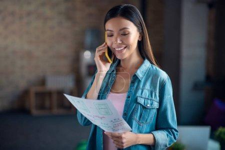 Photo pour Examen du projet. Belle femme positive discutant de son projet tout en ayant un appel au travail - image libre de droit