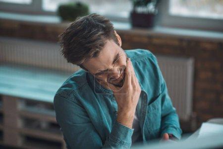 Photo pour Quand finira-t-elle ? Un homme triste et malheureux qui se touche le visage tout en ressentant une très forte douleur - image libre de droit