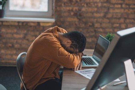 Photo pour Travailler trop. Beau jeune homme fatigué qui s'endort presque en travaillant de longues heures - image libre de droit