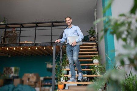 Photo pour Avoir une journée de travail. Un homme debout dans un escalier tenant son ordinateur - image libre de droit