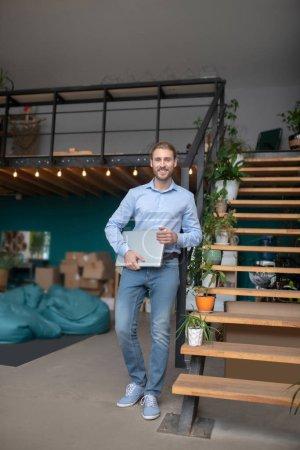 Photo pour Déménagement dans un nouveau bureau. Un homme tenant un ordinateur debout dans un nouveau lieu de travail - image libre de droit
