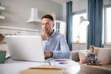Photo pour En pensant. Un homme brandi dans une chemise bleue qui semble bien travailler sur son ordinateur portatif - image libre de droit