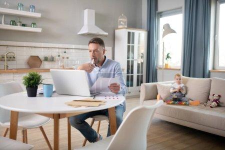 Photo pour Café. Homme porté en chemise bleue, ayant un enfant et travaillant sur son ordinateur portable - image libre de droit